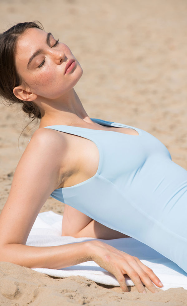 A woman taking the sun on a beach with her light blue swimsuit.