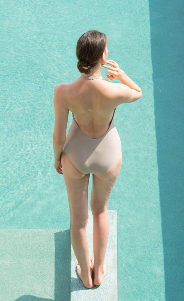 A woman in a swimming pool wearing a beige swimsuit.