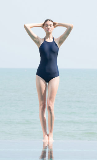 A woman wearing a dark blue one-piece swimsuit.