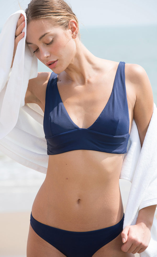 A woman going out of the sea, wearing her Midnight Triangle bikini.