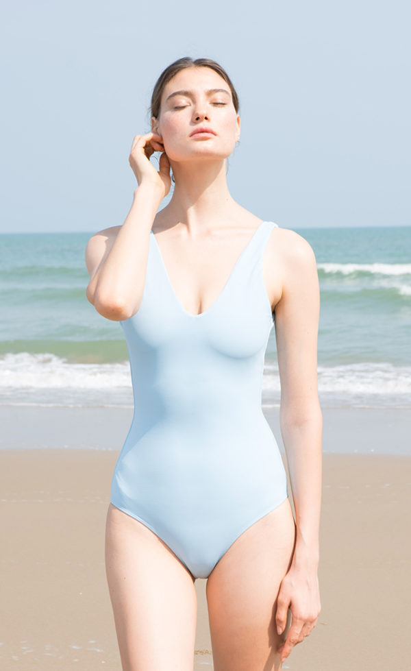 The Classic Swimsuit in Sky color worn on the beach.